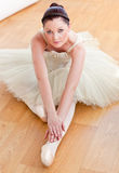 Female ballet dancer stretching in the floor Stock Photography