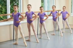 Female ballet dancers posing at barre. Young dancers having practice in classical ballet studio. Five cute ballerinas training at barre Stock Photos