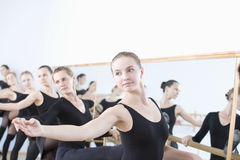 Female Ballet Dancers Practicing At Barre Stock Photo