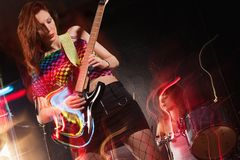 Female band playing on stage. Photo of a young beautiful women playing guitar with drummer in the background.  Motion blur and light trails from slow shutter Royalty Free Stock Photo