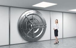Female bank worker standing in front of a big locked round metal Royalty Free Stock Images