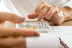Female banker calculating expenses and income using adding machi. Front view of female banker calculating expenses and income using adding machine while checking royalty free stock photos