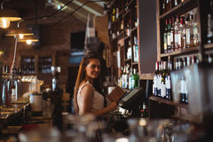 Female bar tender holding menu. Portrait of female bar tender holding menu in pub Royalty Free Stock Image