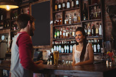 Female bar tender interacting with customer Royalty Free Stock Photography