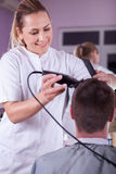Female barber cutting hair with clipper. Smiling women cutting men hair with clipper stock photography