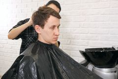 Female barber haircut doing male hair style. Copy space royalty free stock image