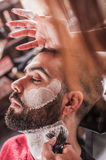 Female barber with shaving brush applied foam to face of client Stock Photo