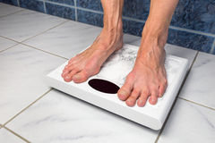 Female bare feet on bathroom scales Royalty Free Stock Photography