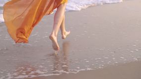 Female bare feet and fluttering dress at sunset. Young barefoot girlrunning in long orage dress along the surf line. Female bare feet and fluttering dress at stock footage