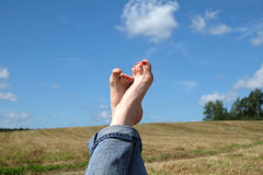 Female bare feet with red nails against summer landscape Stock Photos