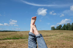 Female bare feet with red nails against summer landscape Royalty Free Stock Photo