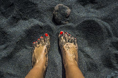 Female bare feet with red nails on black sand beach Stock Photography