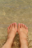 Female bare feet in sea water on sand beach Royalty Free Stock Photography