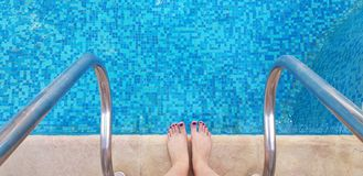 Female bare feet standing on the edge of swimming pool half ready to enter stock images