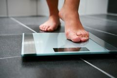 Female bare feet with weight scale. In the bathroom Royalty Free Stock Images