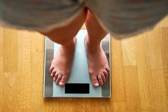 Female bare feet with weight scale. Top view Stock Photography