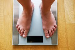 Female bare feet with weight scale. Top view Stock Image