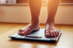 Female bare feet on weight scale. At sunshine Stock Photos