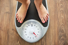 Female bare feet on weight scale. Top view Royalty Free Stock Photo
