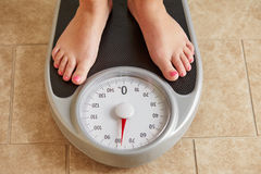 Female bare feet on weight scale. Top view Royalty Free Stock Images