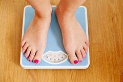 Female bare feet with weight scale. On wooden floor Stock Photos