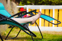 Female bare feet. Woman relaxing on sunbed Stock Photography