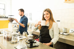 Female barista drinking a cup of coffee. Portrait of a gorgeous young female barista drinking and enjoying a cup of coffee at work Stock Photo
