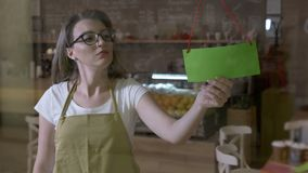 Female barista looking out the window for clients sighing tiered at the end of shift and flipping over green screen closing sign -. Female barista with glasses stock video