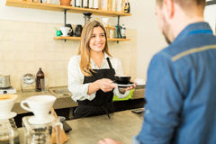 Female barista making coffee for a customer Royalty Free Stock Image