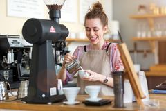 Female barista making coffee stock images