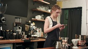 Female barista taking pictures of prepared cofee with smartphone stock video