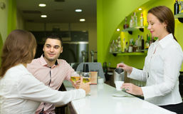 Female barista and two clients in cafe Royalty Free Stock Image