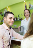 Female barista and two clients in cafe Royalty Free Stock Photos