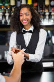 Female barmaid serving a glass of whiskey Stock Images