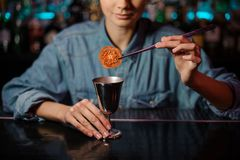 Female bartender adding a dried tomato with tweezers to a cocktail glass with alcoholic drink. On the bar counter on the blurred background stock images