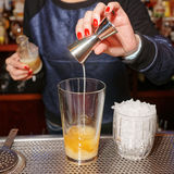 Female bartender is adding an ingredient Stock Image