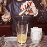 Female bartender is adding an ingredient, toned royalty free stock photo