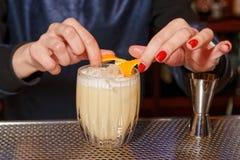 Female bartender is adding orange zest royalty free stock image