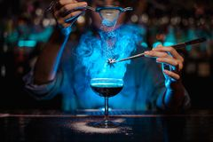 Female bartender adding to a brown cocktail and pour on a flamed badian on tweezers a powdered sugar in the blue light. Female bartender adding to a brown stock photo