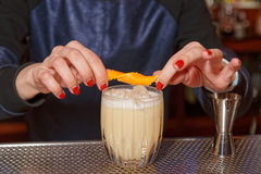 Female bartender is adding zest to cocktail stock image