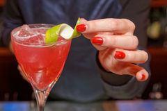 Female bartender is decorating a cocktail stock photos