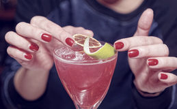Female bartender is decorating a cocktail, toned royalty free stock images