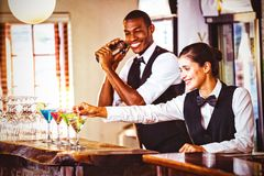 Female bartender garnishing cocktail with olive. Smiling female bartender garnishing cocktail with olive on bar counter royalty free stock photo