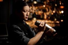 Female bartender holding shaker at bar counter. Cute female bartender holding stainless steel shaker at bar counter stock image