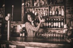 Female bartender mixing a cocktail drink in cocktail shaker. At counter stock photos