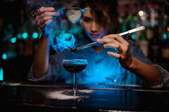 Female bartender pouring on the brown cocktail and on a flamed badian on tweezers a powdered sugar in the blue light. Female bartender pouring on the brown stock image
