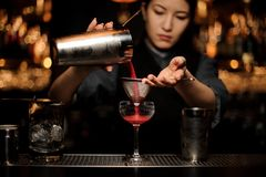 Female bartender pouring cocktail with shaker and sieve. Attractive female bartender pouring an alcohol cocktail with steel shaker and sieve at the bar counter stock images
