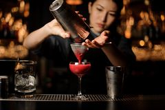 Female bartender pouring a cocktail with the shaker and sieve. Attractive female bartender pouring an alcohol cocktail with the metal shaker and sieve at the bar royalty free stock image