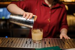 Female bartender pouring a fresh cocktail into the glass. Female bartender pouring a fresh alcoholic cocktail from shaker into the glass on the bar counter royalty free stock photography