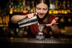 Female bartender pouring out a cocktail from the shaker through the sieve. Female bartender pouring out a fresh delicious white cocktail from the steel shaker royalty free stock images